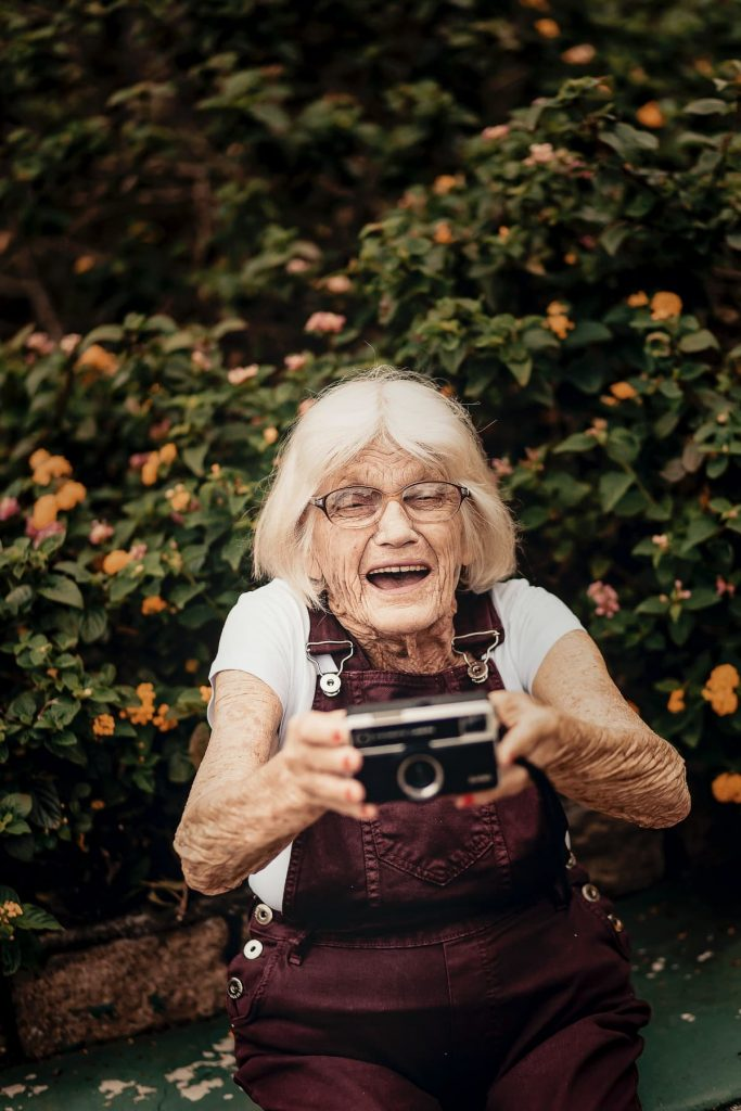 lachende alte Frau mit Kamera